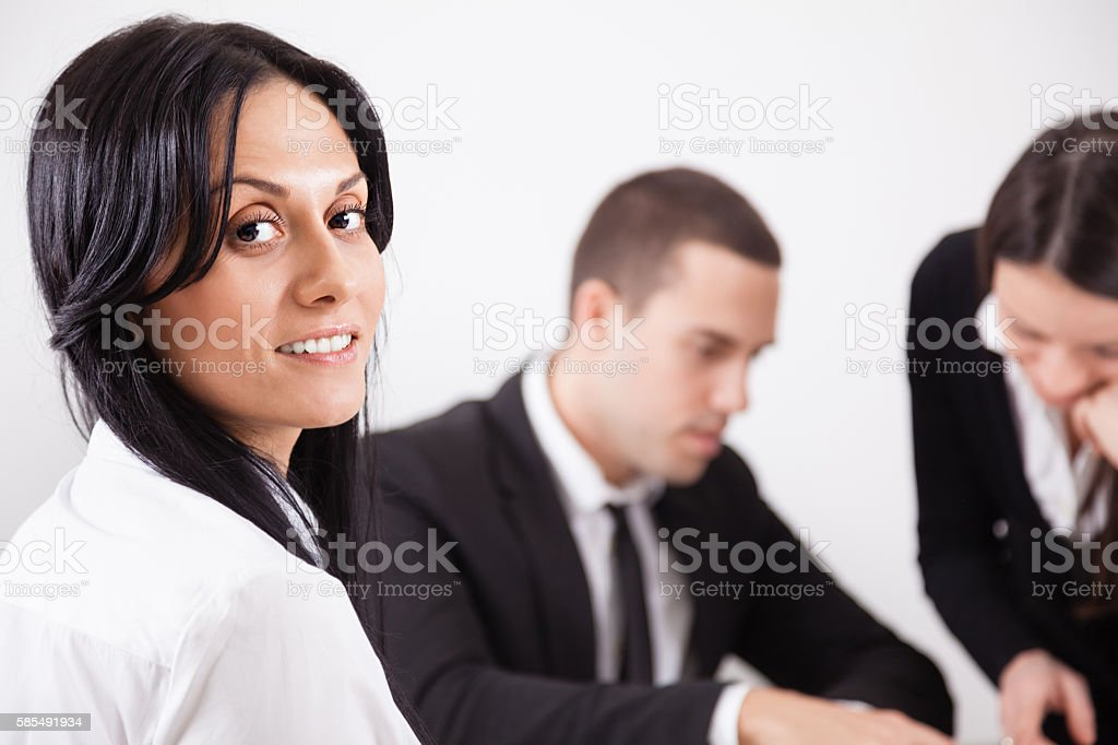 Happy young business woman with colleagues stock photo