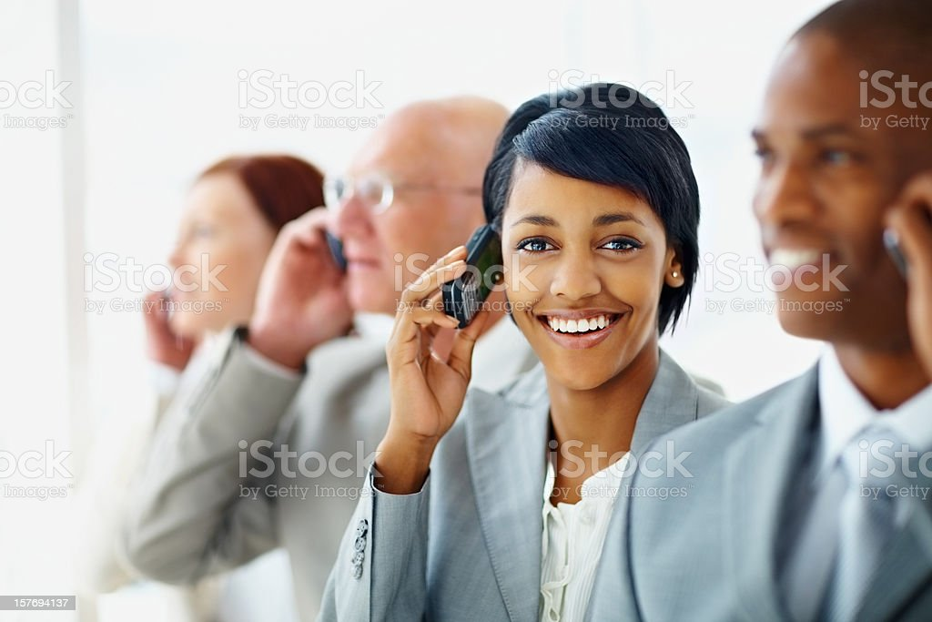 Happy young business woman with her team over the cellphones royalty-free stock photo
