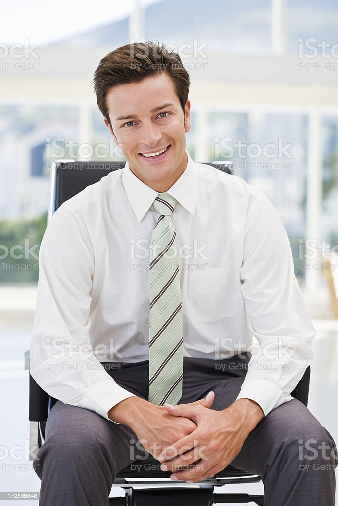 Happy young businessman sitting on chair in office royalty-free stock photo