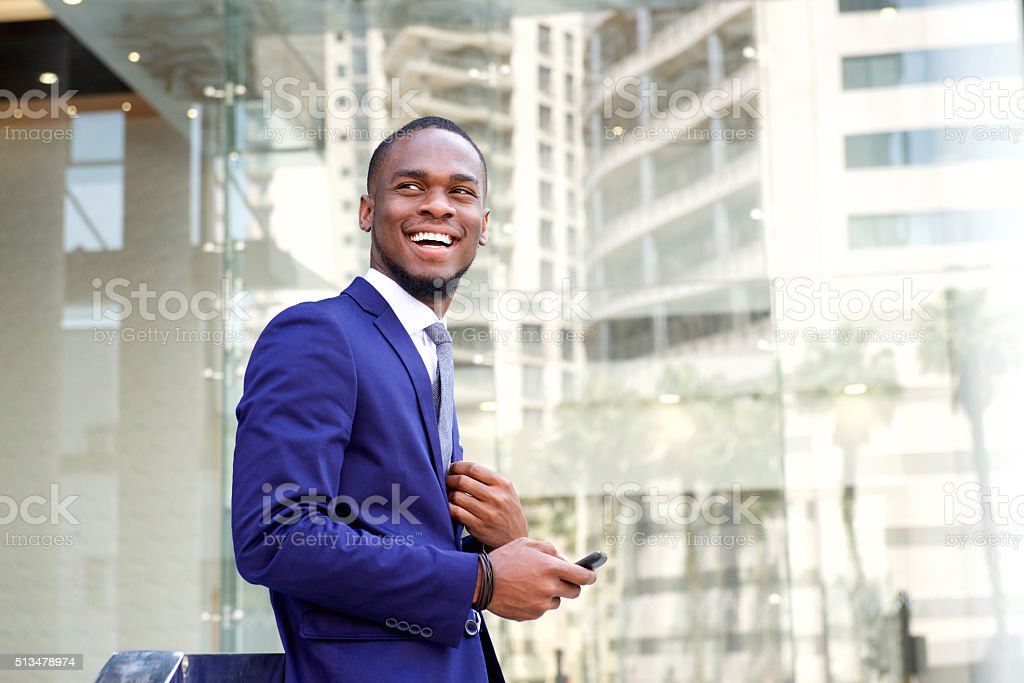 Happy young businessman standing in the city stock photo