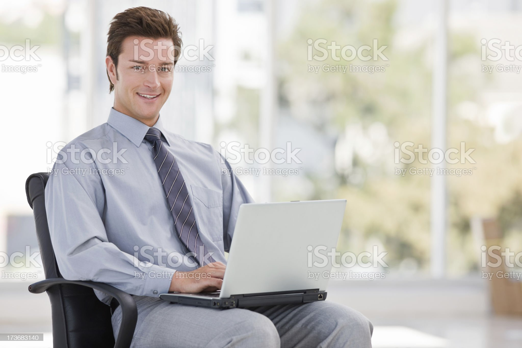 Happy young businessman using laptop royalty-free stock photo