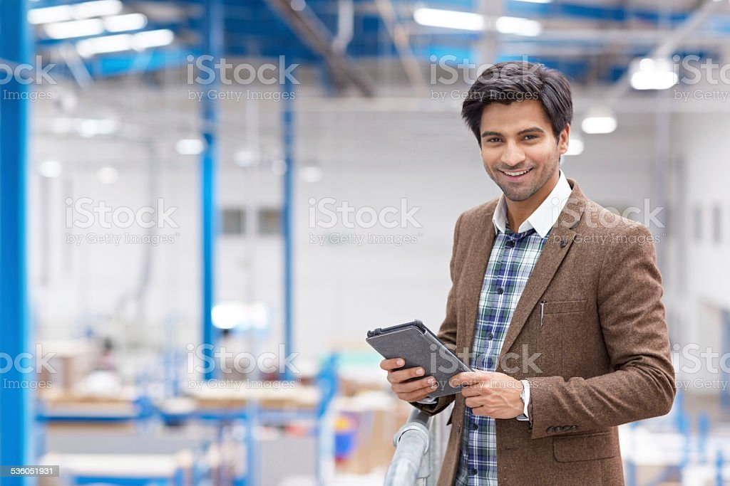 Happy young businessman with digital tablet in warehouse stock photo