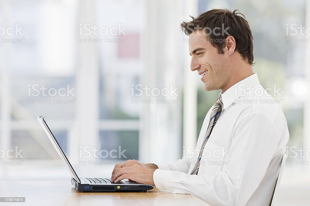 Happy young businessman working on laptop in office royalty-free stock photo