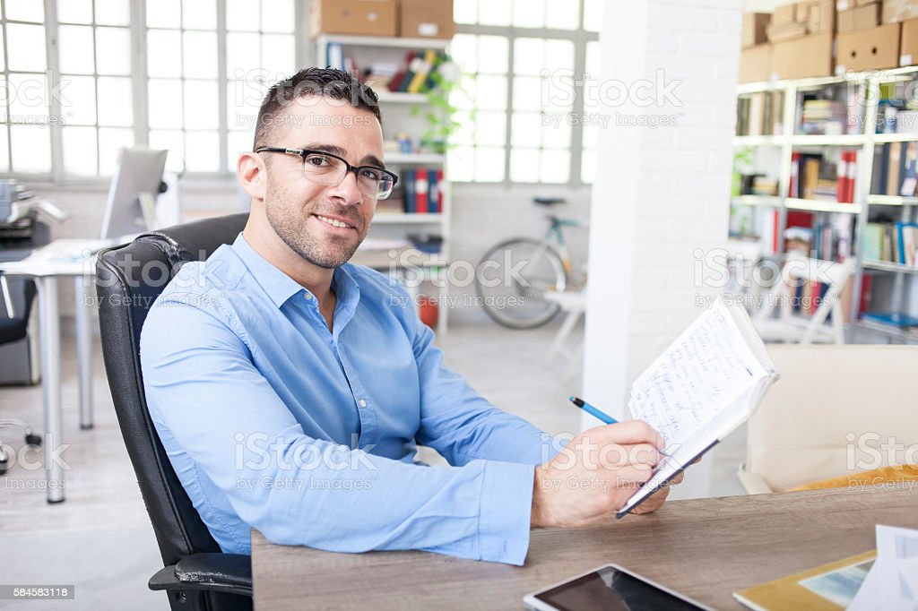 Happy young businessman writing notes stock photo