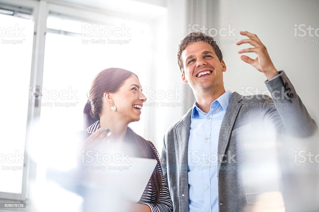 Happy young businesswoman looking at male colleague in office stock photo