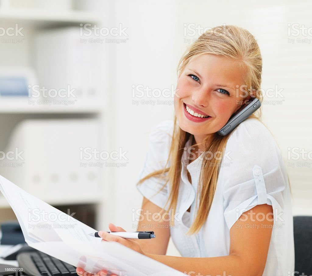 Happy young businesswoman talking on a cellphone royalty-free stock photo