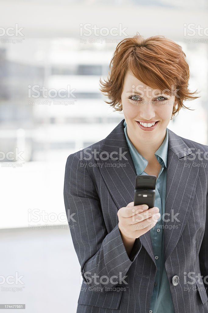 Happy young businesswoman text messaging on cellphone royalty-free stock photo