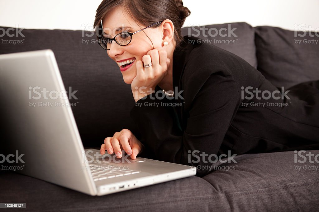 Happy Young Businesswoman Using Laptop Computer on Couch at Home royalty-free stock photo