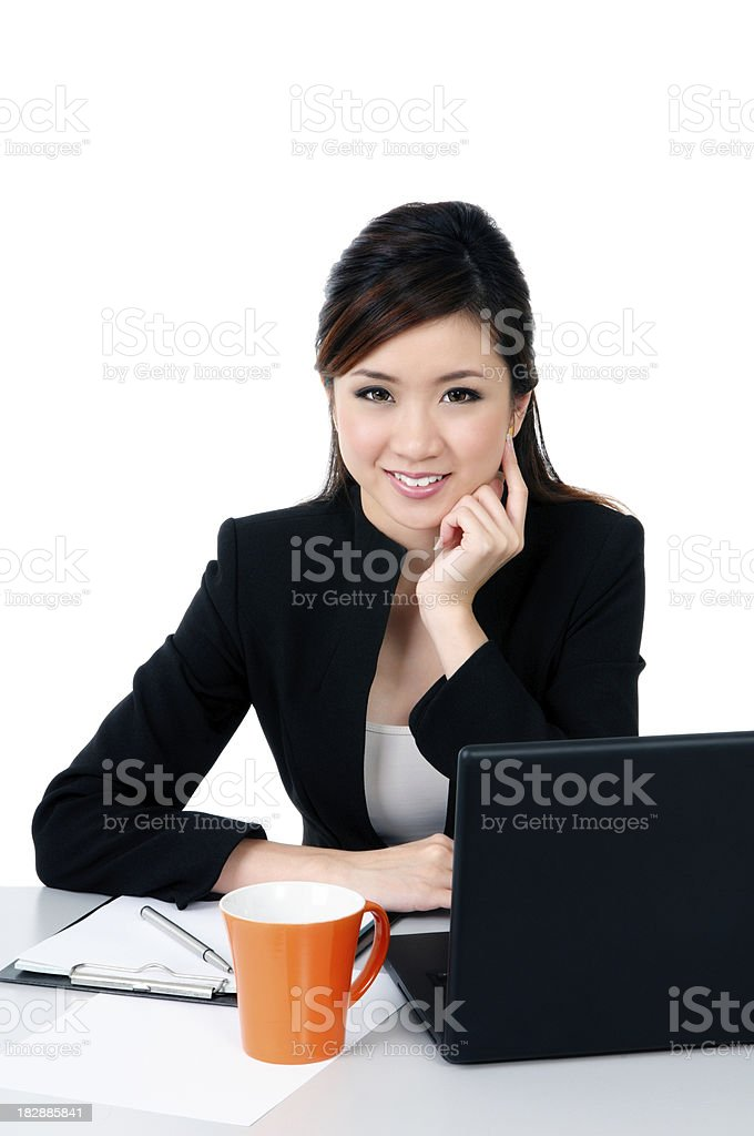 Happy young busineswoman at office desk stock photo