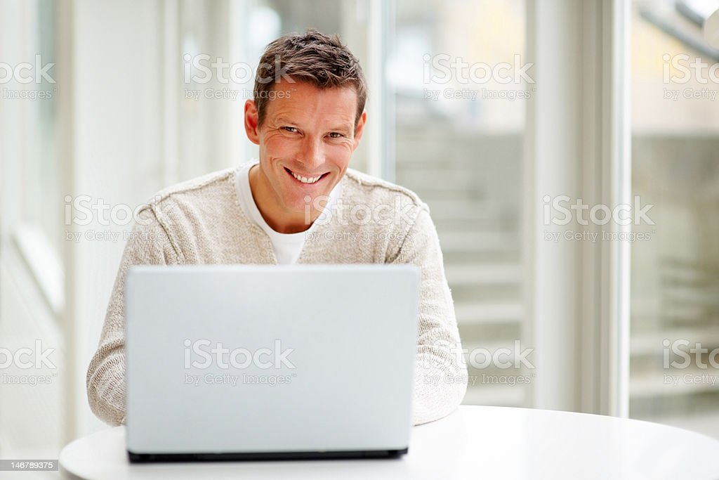 Happy young casual businessman working on laptop royalty-free stock photo