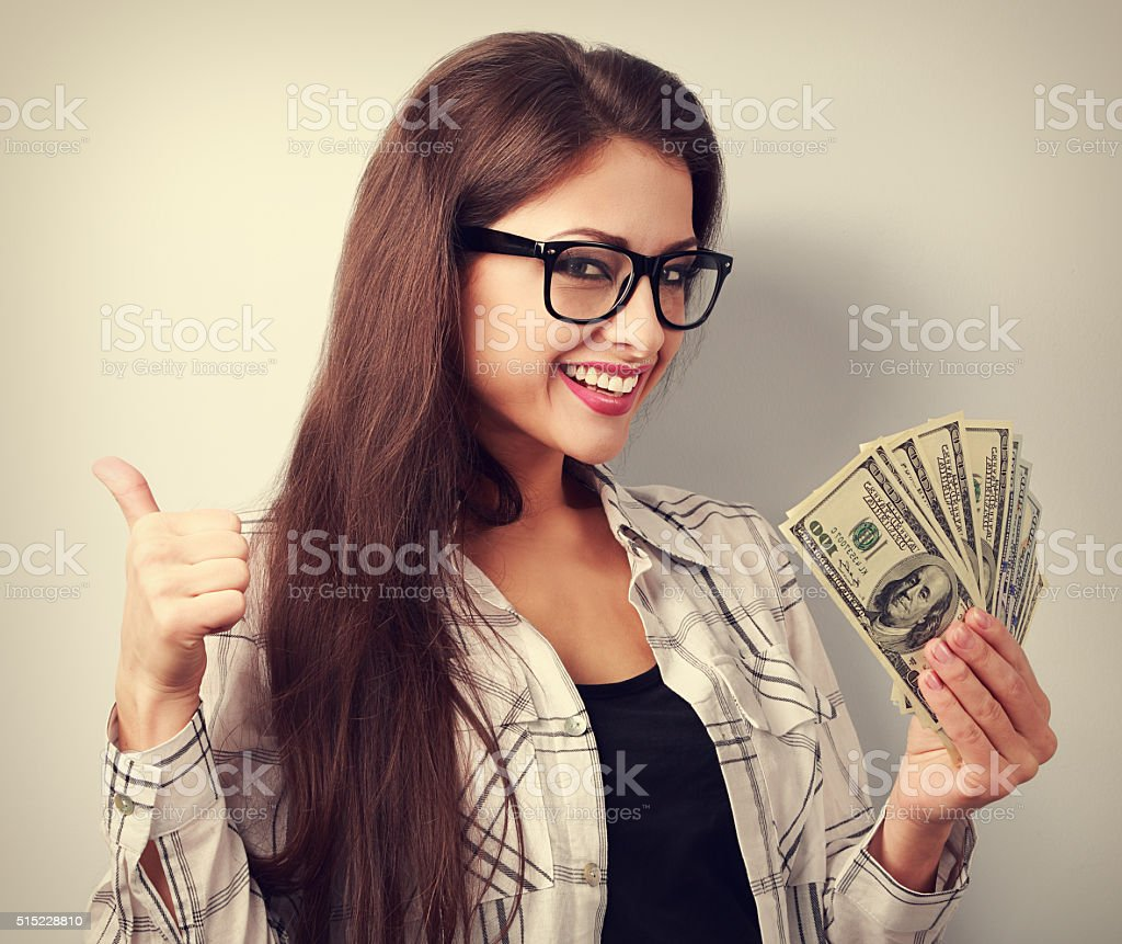 Happy young casual woman in glasses holding dollars and showing stock photo