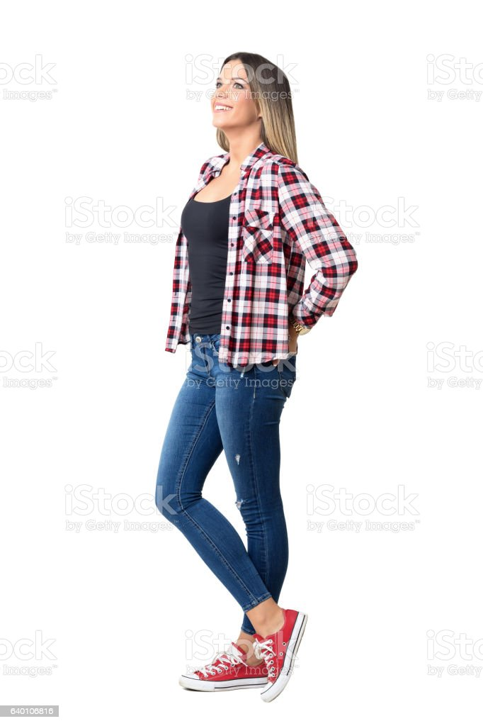 Happy young casual woman wearing jeans looking up smiling stock photo