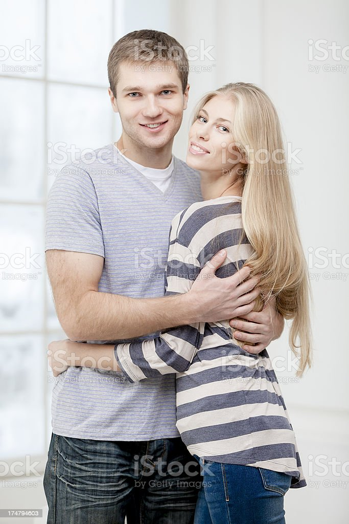 happy young caucasian couple hugging indoors royalty-free stock photo