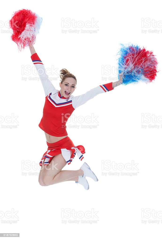 Happy Young Cheerleader Jumping With Pom-poms stock photo