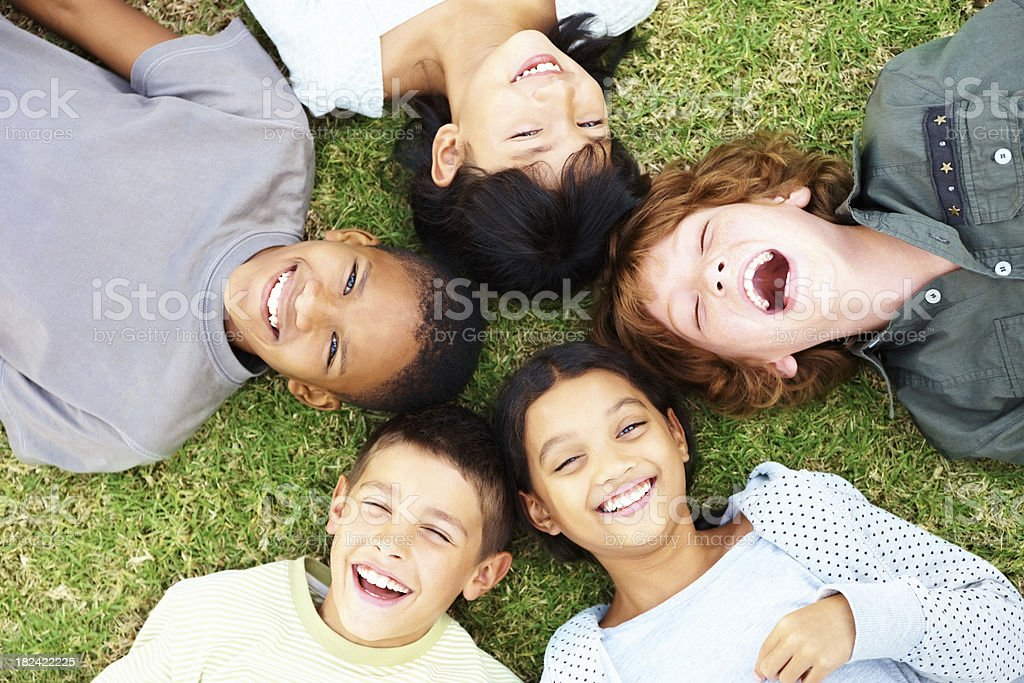 Happy young children lying on grass and laughing royalty-free stock photo