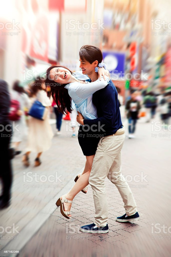 Happy Young couple against cityscape background, Tokyo. stock photo
