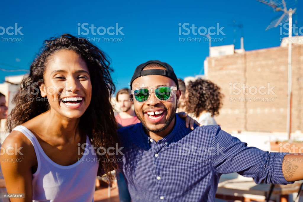 Happy young couple at rooftop party stock photo