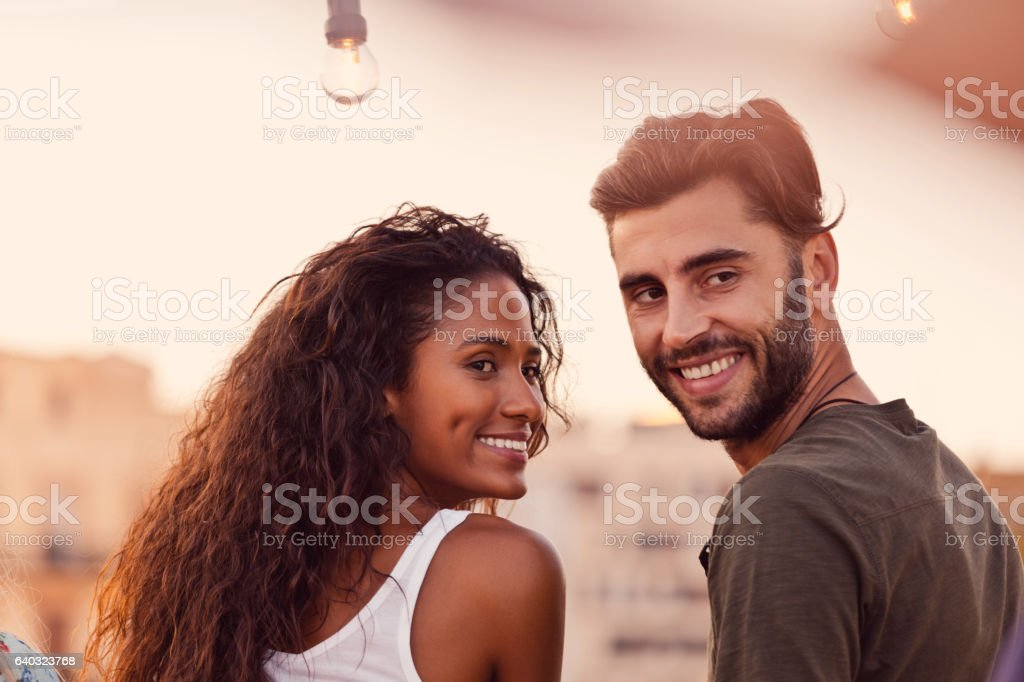 Happy young couple at the rooftop party stock photo