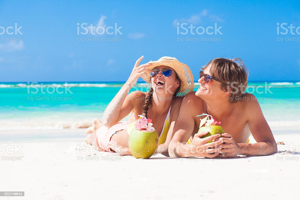 happy young couple at tropical beach in Barbados with coconuts stock photo