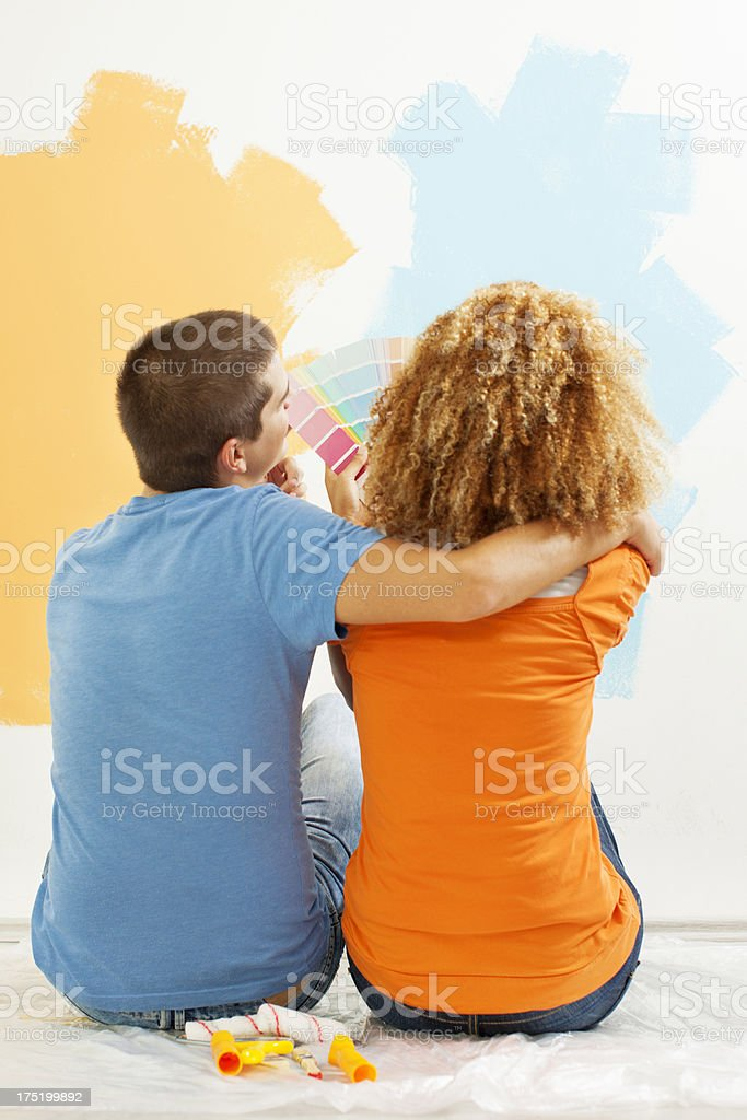 Happy Young Couple Choosing Paint Color for Their Home royalty-free stock photo