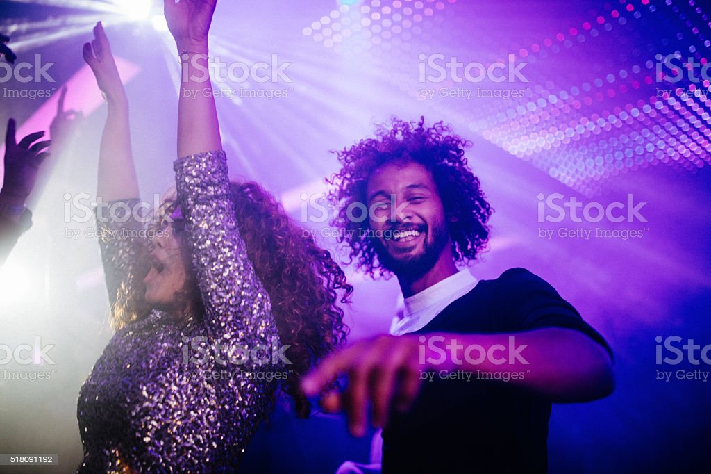 Happy young couple dancing in a night club stock photo
