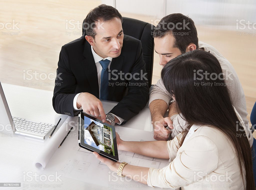 Happy Young Couple Discussing With Consultant stock photo