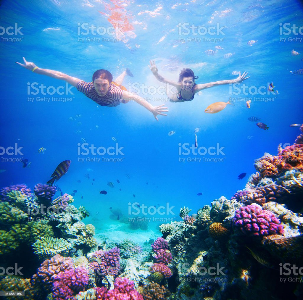 Happy young couple diving in super clear tropical sea stock photo