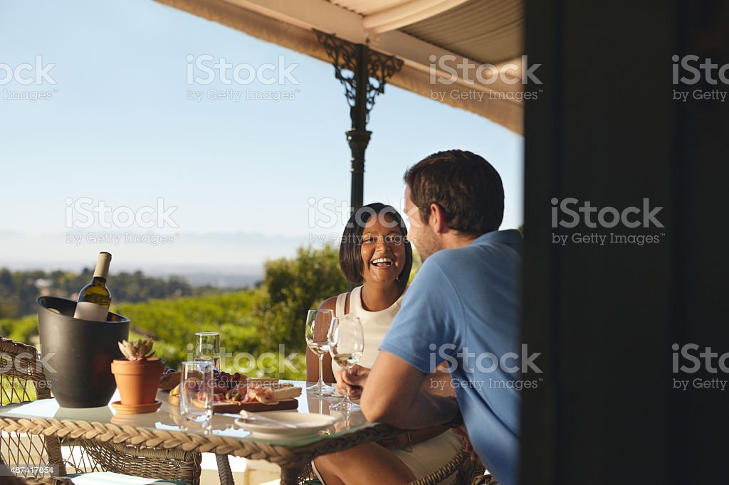 Happy young couple drinking wine at winery stock photo