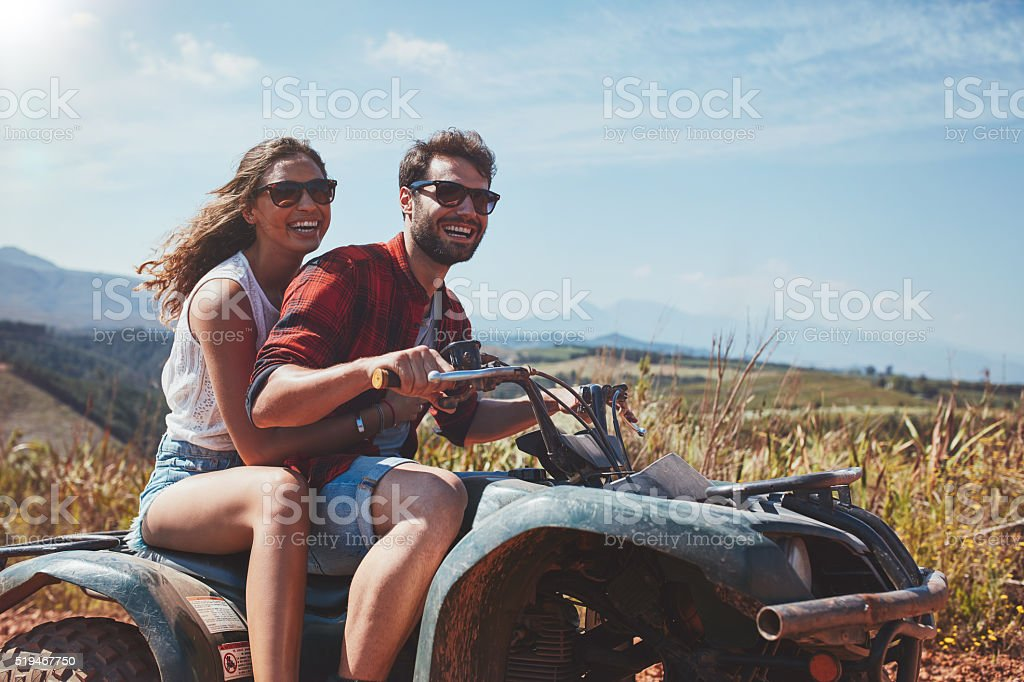Happy young couple driving a quad bike stock photo