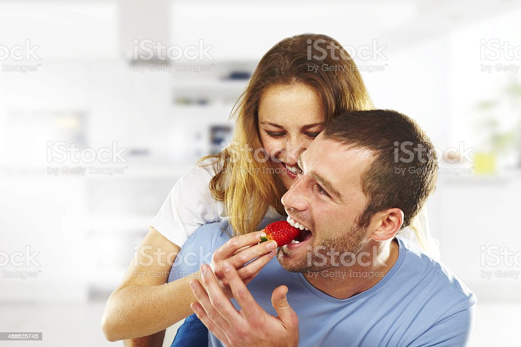Happy young couple eating strawberries together. stock photo
