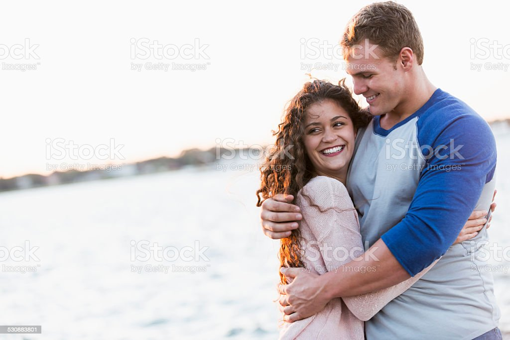 Happy young couple embracing by the water stock photo