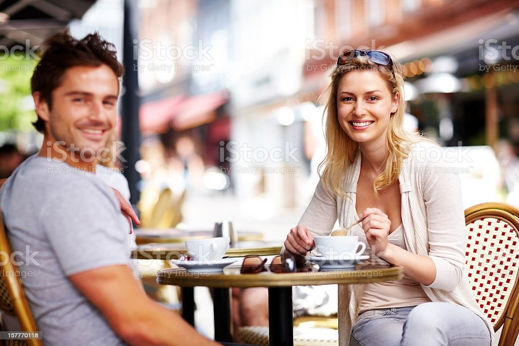 Happy young couple enjoying coffee at a open cafe royalty-free stock photo