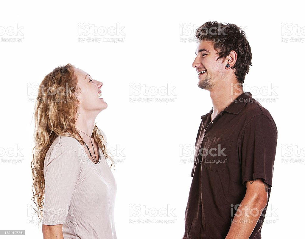 Happy young couple face each other laughing stock photo