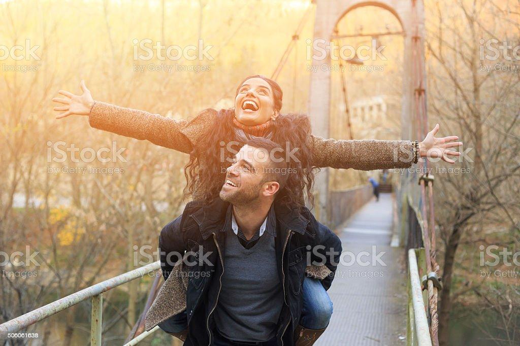 Happy young couple flying on bridge stock photo