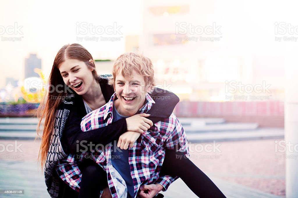 Happy young couple having fun on piggy back, Tokyo. stock photo