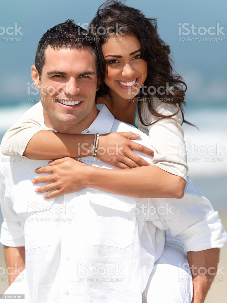 Happy young couple having fun on the beach royalty-free stock photo