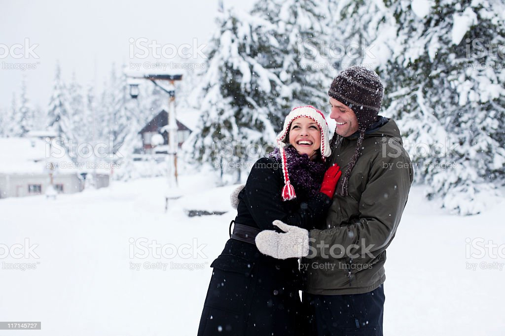Beautiful Young Couple Embracing in Winter Snow, Copy Space royalty-free stock photo