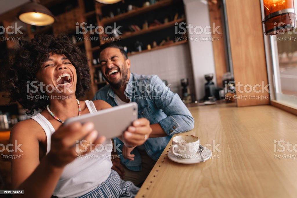 Happy young couple having fun with phone at cafe stock photo