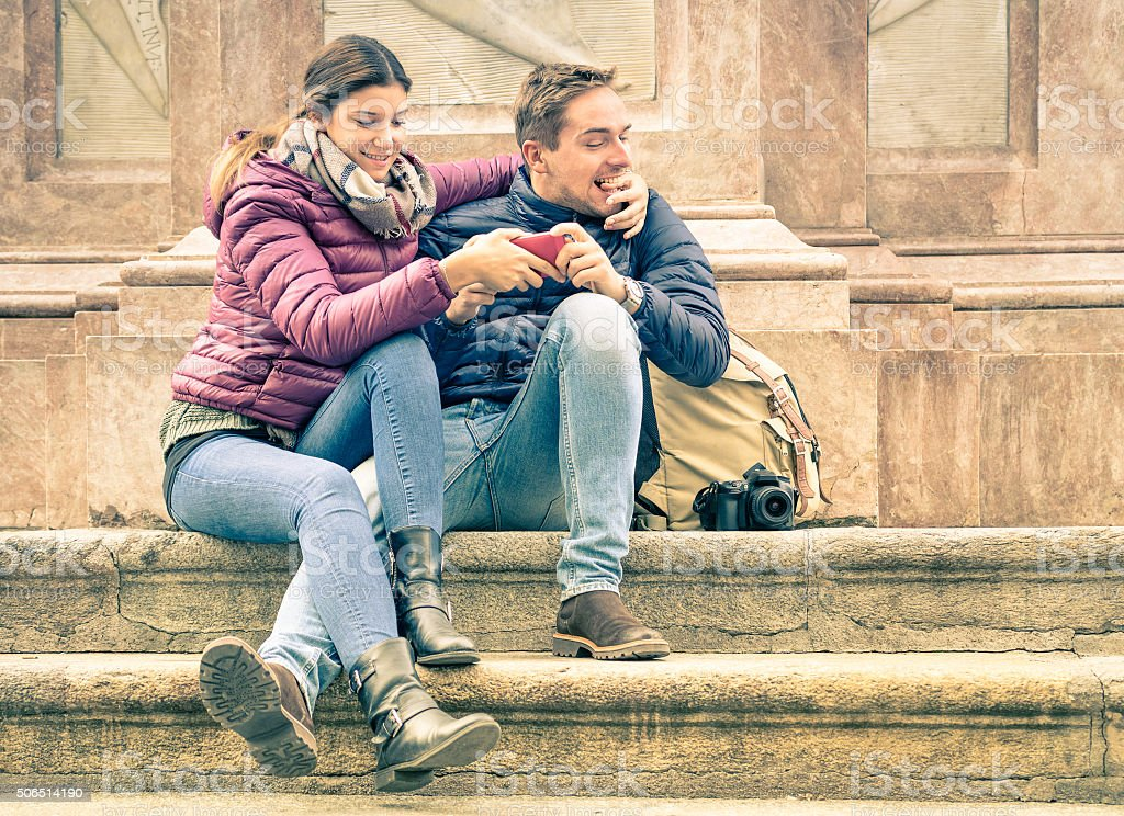 Happy young couple having fun with smartphone outdoors stock photo