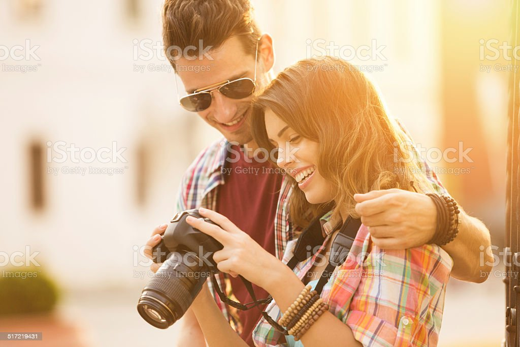 Happy young couple holding a camera stock photo