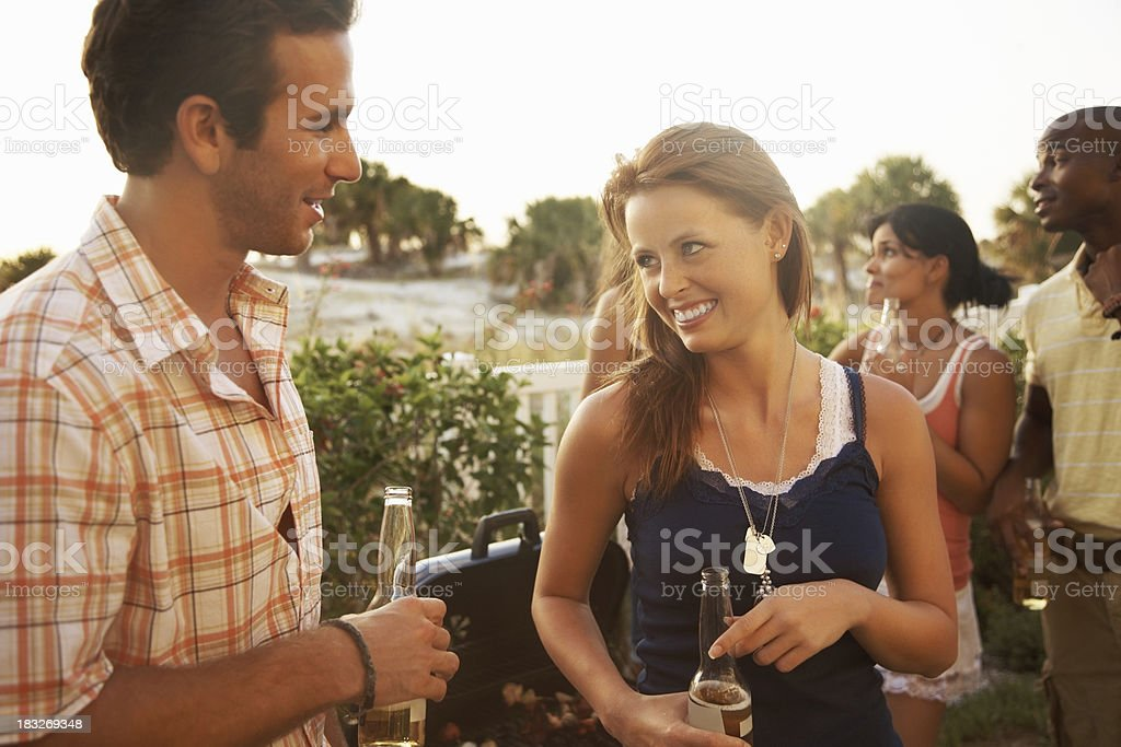 Happy young couple holding beer and their friends in background royalty-free stock photo