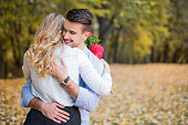 Happy young couple hugging in the park on fallen leaves