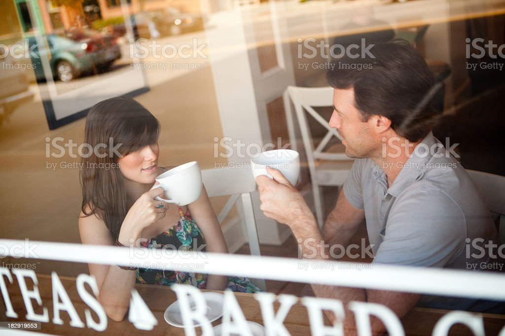 Happy Young Couple in Cafe Seen Through Window royalty-free stock photo
