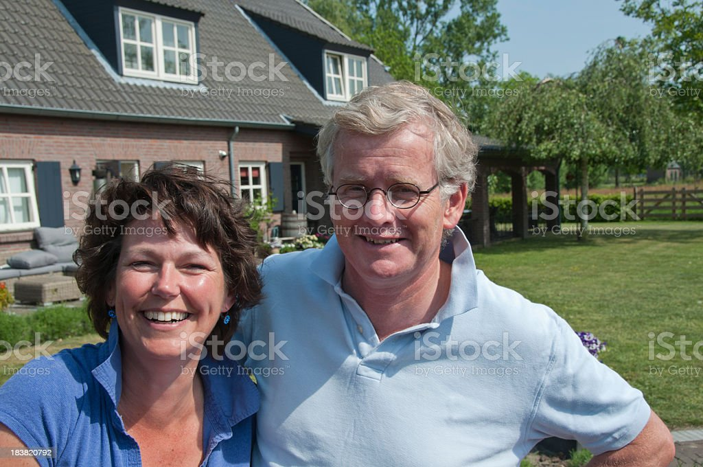 Happy young couple in front of their house sunny garden stock photo