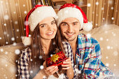 Happy young couple in santa hats holding a christmas present