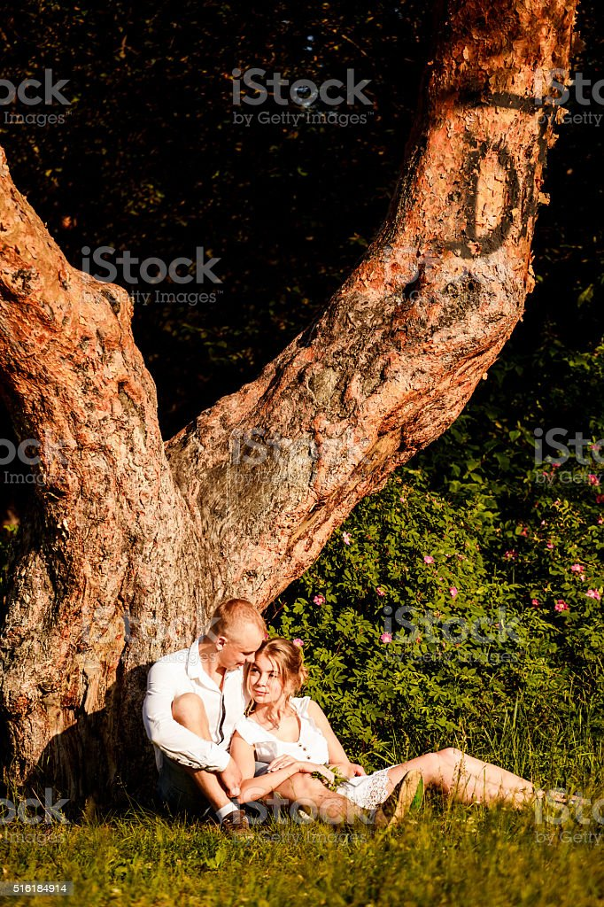 Happy young couple in summer park near a big tree stock photo