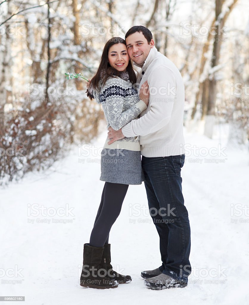 Happy young couple in the winter park stock photo