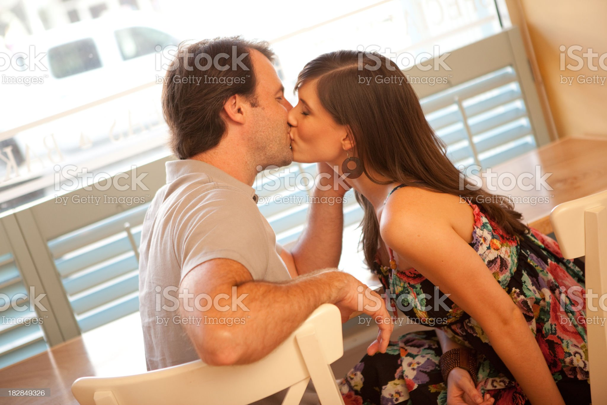 Happy Young Couple Kissing Each Other in Cafe royalty-free stock photo