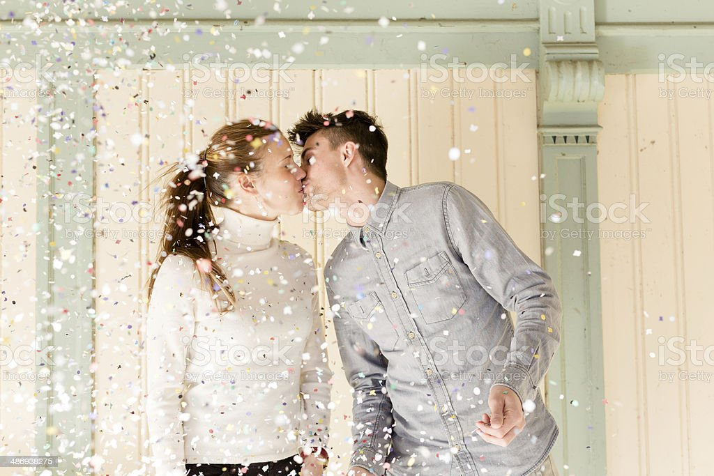 Happy young couple kissing under confetti rain royalty-free stock photo
