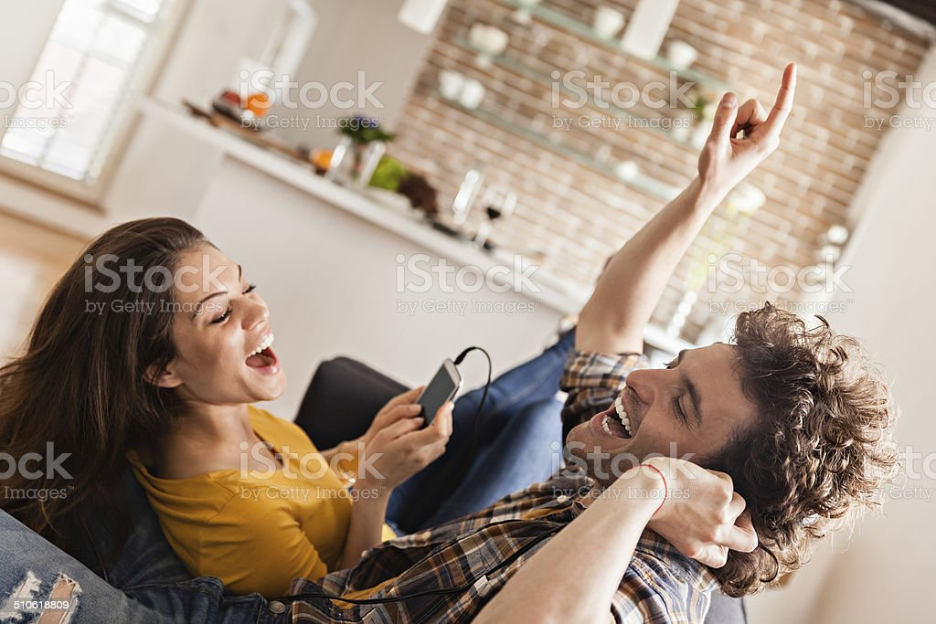 Happy young couple listening to music stock photo